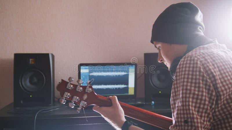 De jonge mannelijke musicus stelt en registreert sound-track samen spelend de gitaar gebruikend computer, hoofdtelefoons en toets stock afbeelding