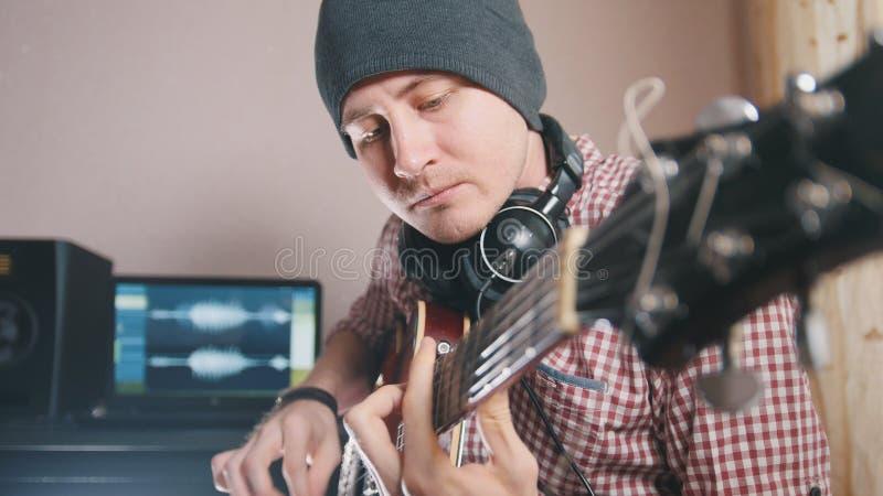 De jonge mannelijke musicus stelt en registreert sound-track samen spelend de gitaar gebruikend computer, hoofdtelefoons en toets royalty-vrije stock afbeeldingen