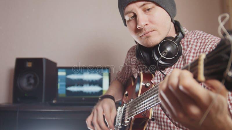 De jonge mannelijke musicus stelt en registreert sound-track samen spelend de gitaar gebruikend computer, hoofdtelefoons en toets stock foto