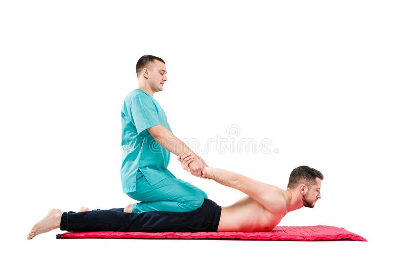 De jonge mannelijke ontvangende massage door therapeut in traditionele Thaise positie inzake wit isoleerde achtergrond royalty-vrije stock afbeeldingen