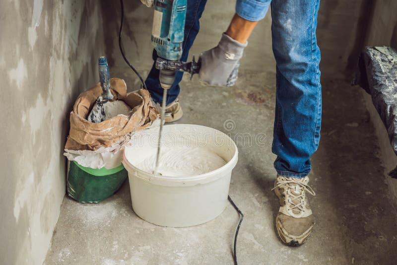 De jonge mannelijke schilder kneedt stopverf met water in een emmer gebruikend een handbediende mixer voor de bouw van mengelinge stock fotografie