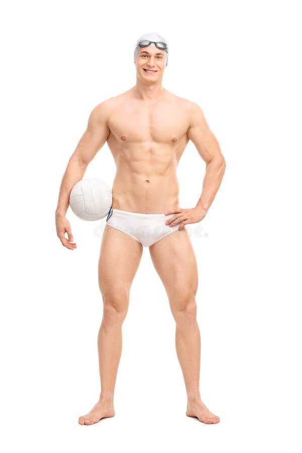 De jonge mannelijke speler die van het waterpolo een bal houden stock foto