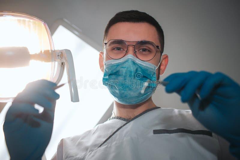 De jonge mannelijke tandarts kijkt op camera Hij draagt witte rob en blauw masker De tandenmateriaal van de kerelgreep voor behan stock foto's