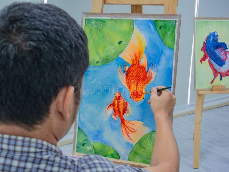 De jonge Mannelijke verf van de waterverfvissen van de kunstenaarstekening stock afbeelding