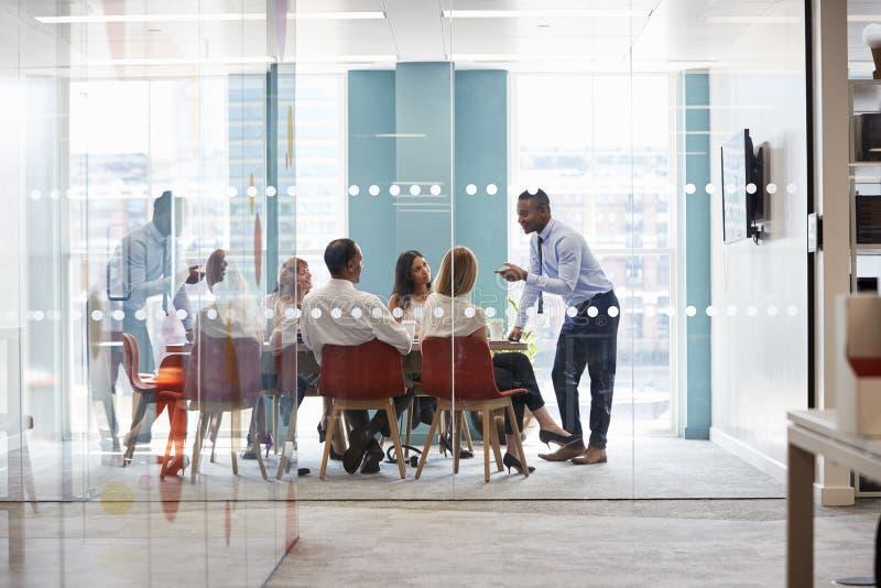De jonge mannelijke werkgever bevindt zich leunend op lijst op commerciële vergadering stock foto's
