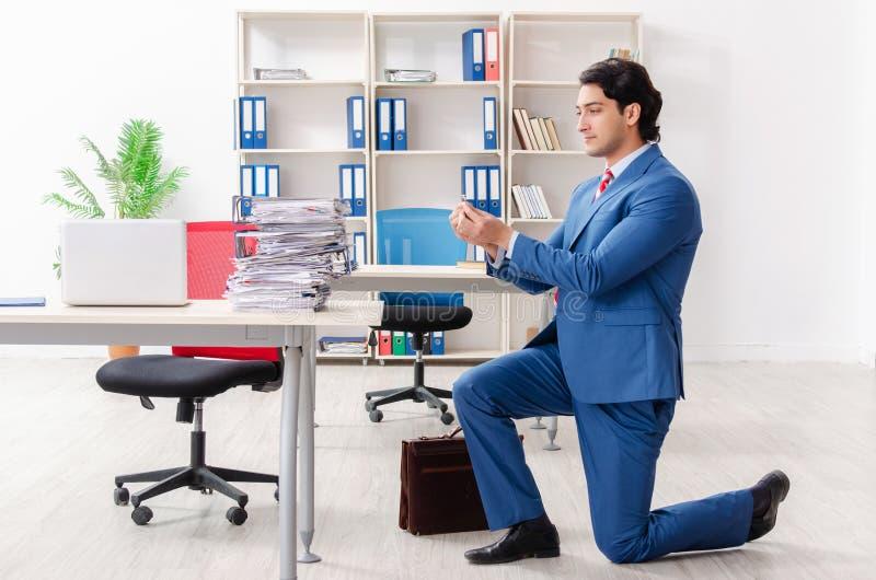 De jonge mannelijke werknemer met verlovingsring in het bureau stock fotografie