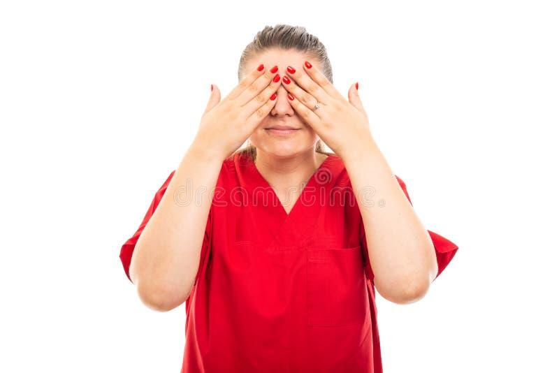 De jonge medische verpleegster die rood dragen schrobt het behandelen van ogen stock fotografie