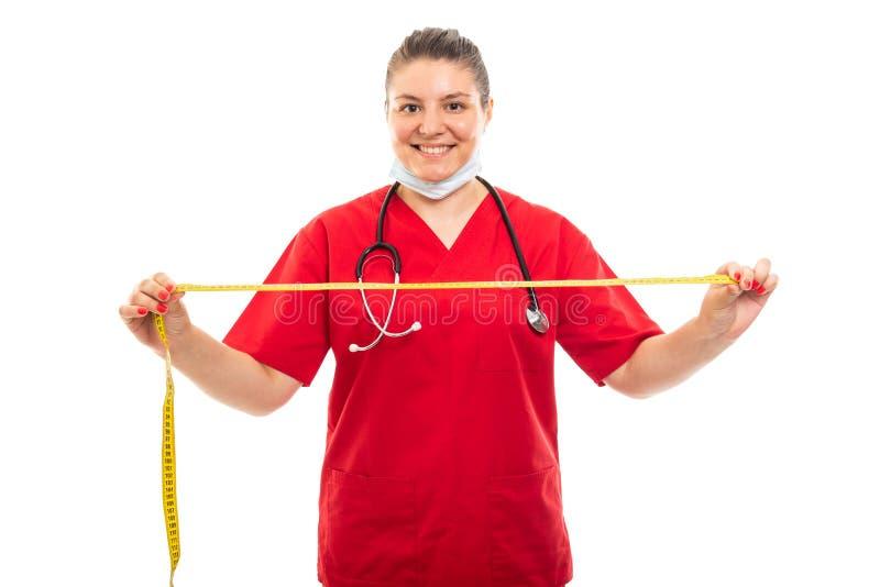 De jonge medische verpleegster die rood dragen schrobt het tonen metend band stock foto