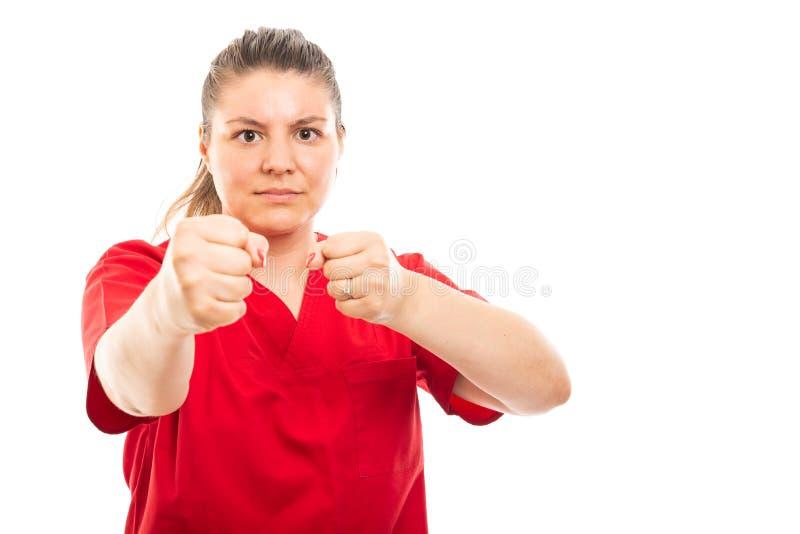 De jonge medische verpleegster die rood dragen schrobt het tonen van beide vuistengebaar royalty-vrije stock foto's