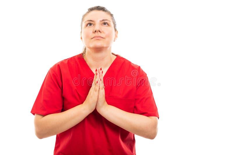 De jonge medische verpleegster die rood dragen schrobt het tonen van het bidden gebaar stock afbeelding