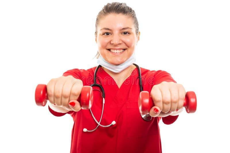 De jonge medische verpleegster die rood dragen schrobt holdingsdomoren stock foto