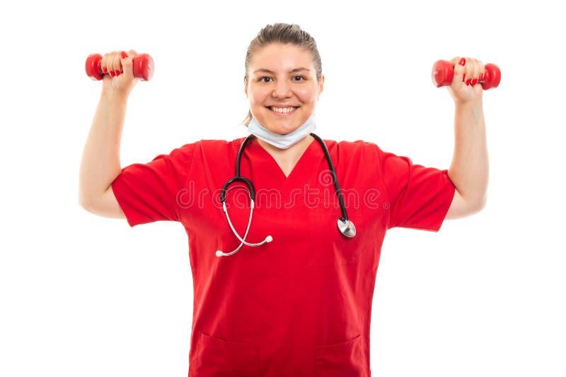 De jonge medische verpleegster die rood dragen schrobt opheffende domoren royalty-vrije stock foto