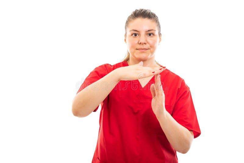 De jonge medische verpleegster die rood dragen schrobt uit het tonen van tijdgebaar royalty-vrije stock foto's
