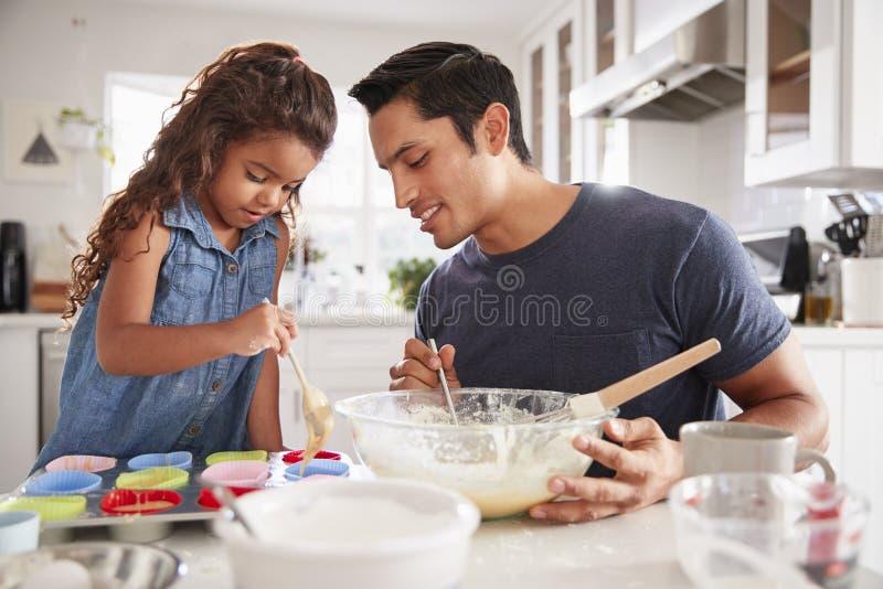 De jonge meisje status bij de keukenlijst die cakes met haar vader maken, die cakevormen vullen, sluit omhoog royalty-vrije stock foto