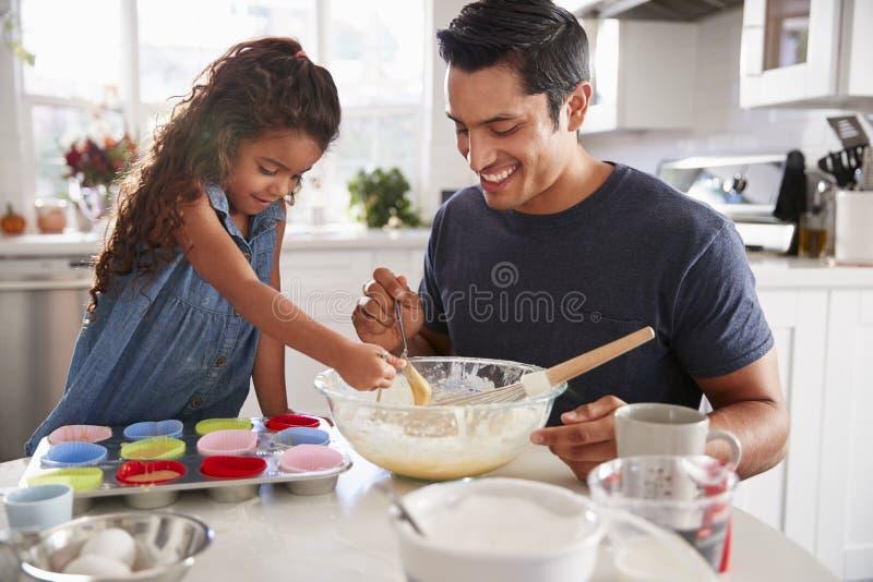 De jonge meisje status bij de keukenlijst die een cakemengeling met haar vader voorbereiden, sluit omhoog stock afbeeldingen
