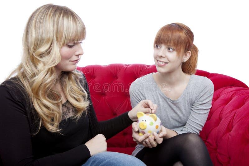 De jonge meisjes besparen geld in piggybank stock foto's