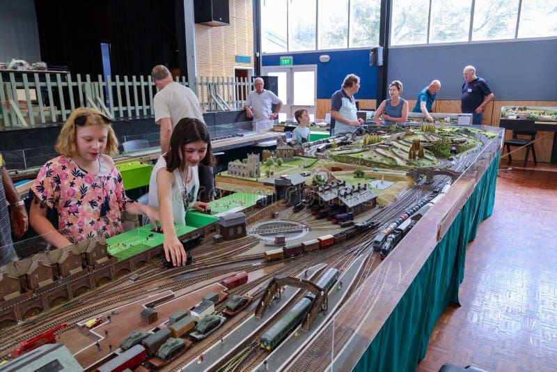 De jonge meisjes die met treinen bij een modelspoorweg spelen tonen stock foto