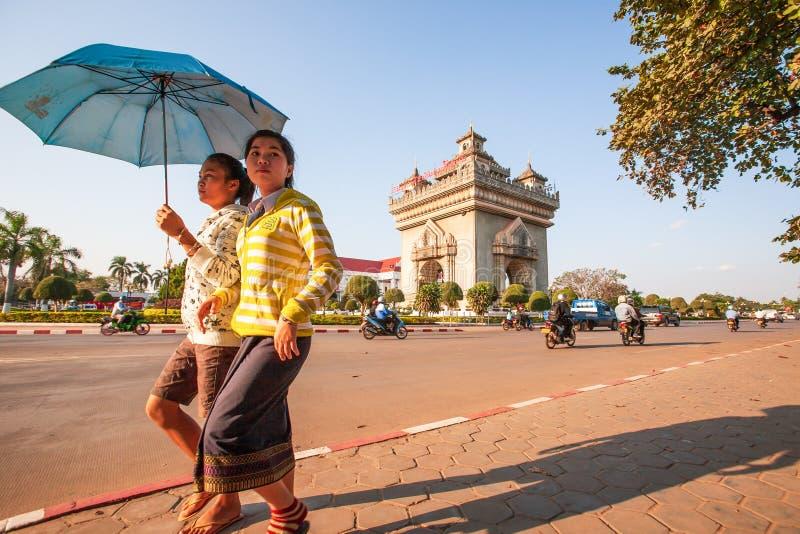 De jonge meisjes die van paarlaos in lao traditionele kleding voorbij lopen royalty-vrije stock foto's