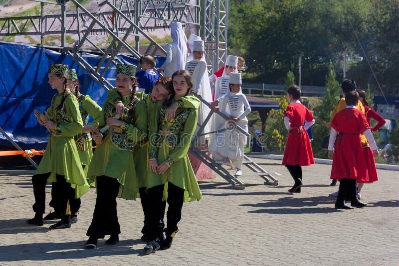 De jonge meisjes en de jongenskunstenaars in traditionele Circassian-kleren treffen om bij het festival van Adyghe-kaas in FO te  stock afbeeldingen