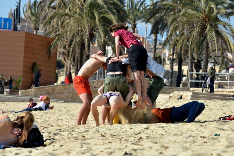 De jonge meisjes en de kerels genieten van en ontspannen in Palma de Mallorca-strand stock foto's