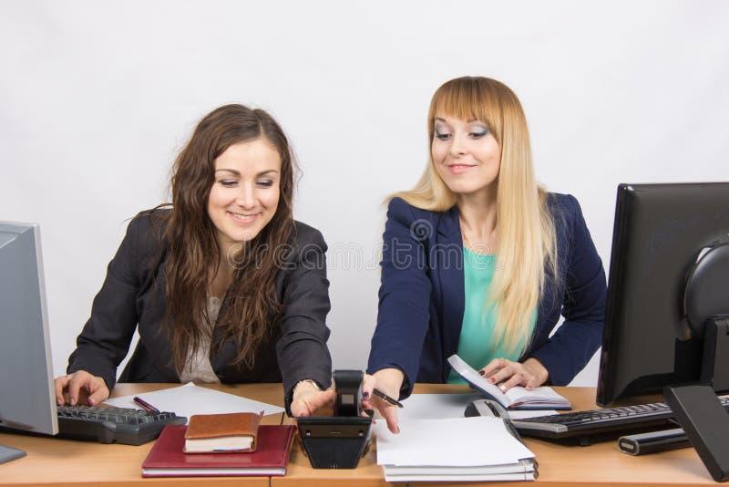 De jonge meisjes in het bureau trekken tegelijkertijd de hand om de telefoon te nemen belden stock afbeelding