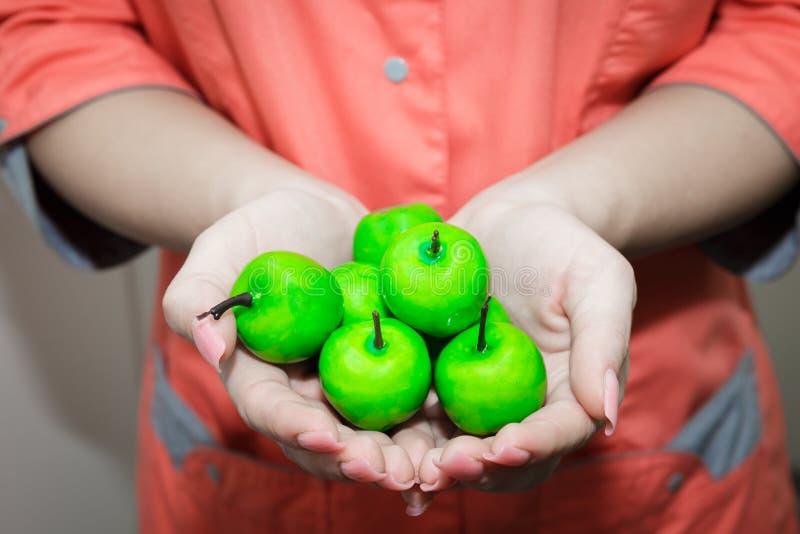 De jonge meisjes overhandigen het houden van klein groen Apple De voedingsdeskundige adviseert appelen royalty-vrije stock afbeelding