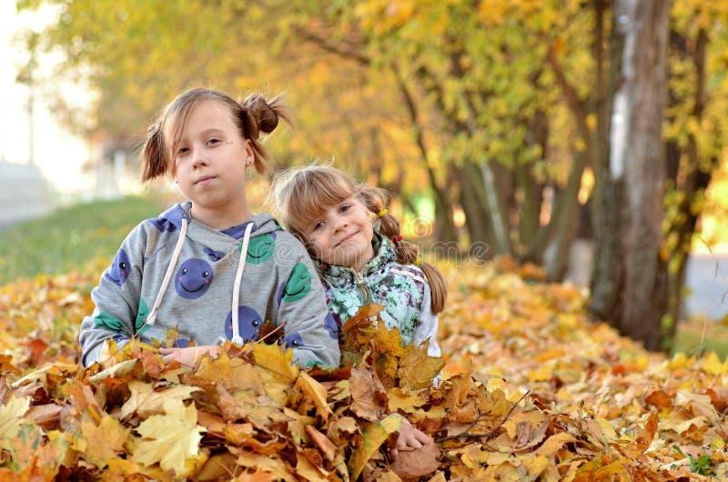 De jonge meisjes spelen in openlucht in het de herfstseizoen stock afbeelding