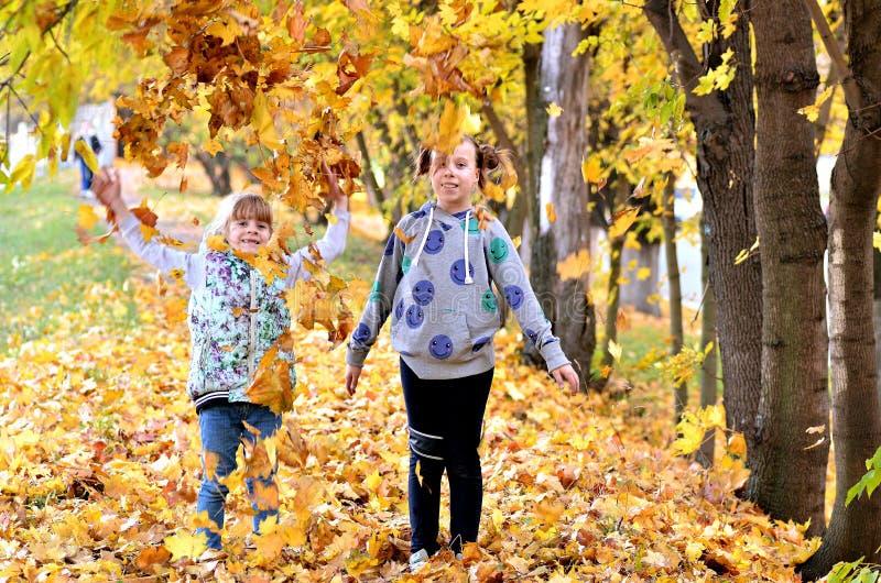 De jonge meisjes spelen in openlucht in het de herfstseizoen stock foto's