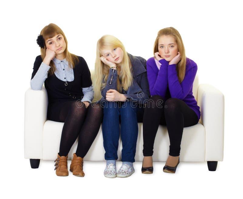 De jonge meisjes zijn droevige zitting op laag stock fotografie
