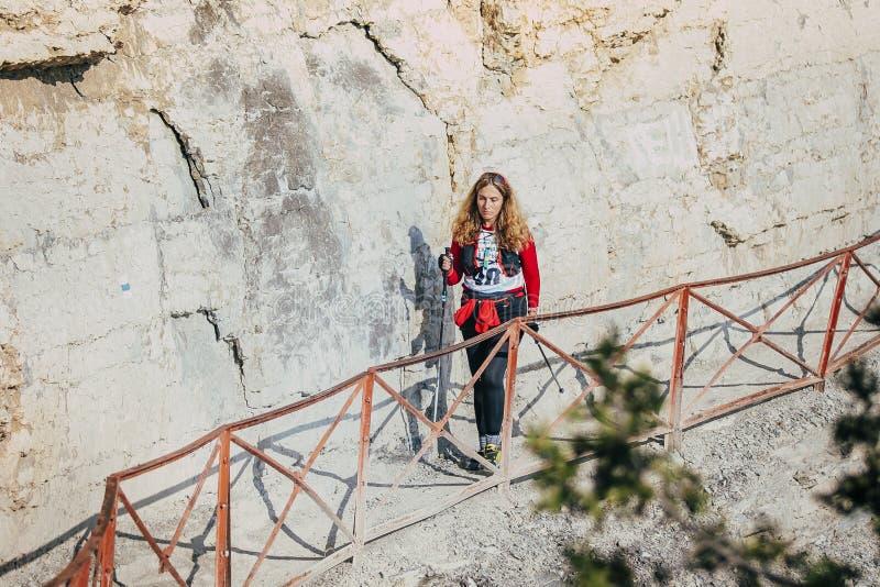 De jonge meisjesatleet gaat op sleep langs klippenrotsen royalty-vrije stock afbeelding