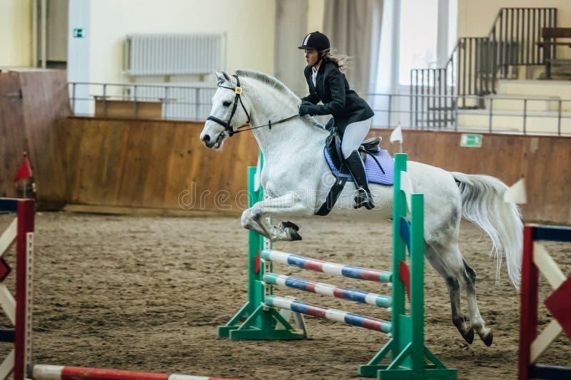 De jonge meisjesatleet op horseback overwint hindernissen in complexe sporten royalty-vrije stock fotografie
