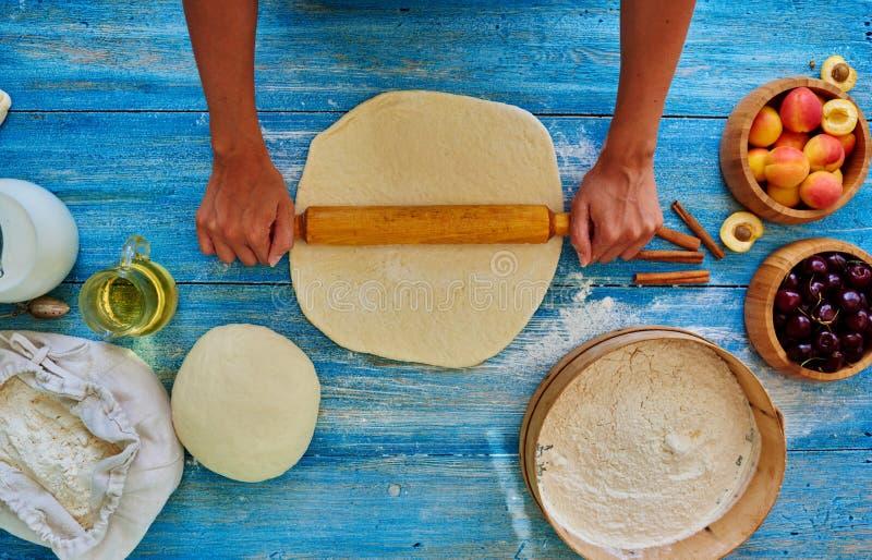 De jonge meisjeschef-kok kneedt en rollend het deeg met speld stock afbeelding