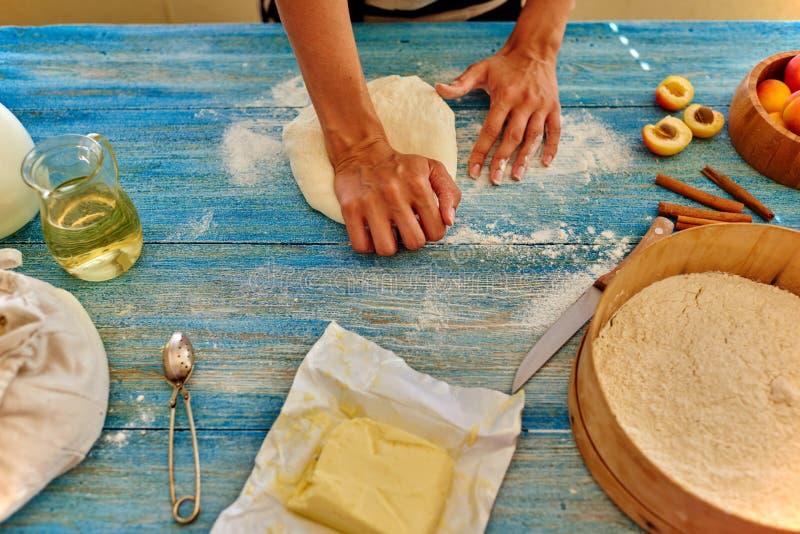 De jonge meisjeschef-kok kneedt en rollend het deeg met speld stock foto's