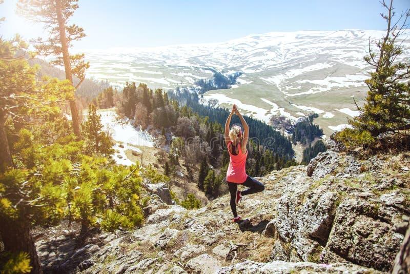 De jonge meisjesreiziger zit bovenop een berg in een yoga stelt Het meisje houdt van te reizen Concept voor reizigers Mening van  royalty-vrije stock afbeeldingen