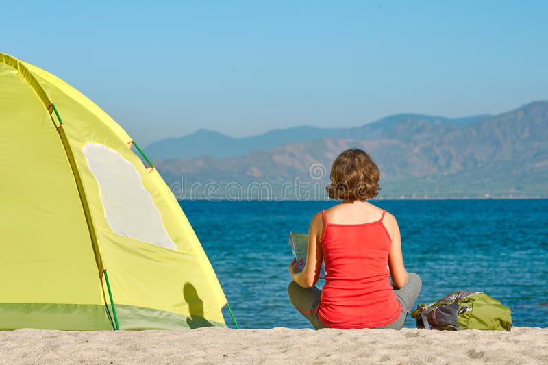 De jonge meisjestoerist zit dichtbij de tent kijkend de kaart stock foto's