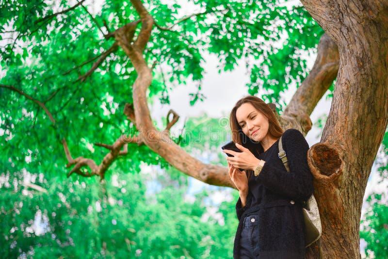 De jonge meisjestribunes bij een grote groene boom met een smartphone in haar handen, communiceert op de Internet-berichten, de m stock afbeelding