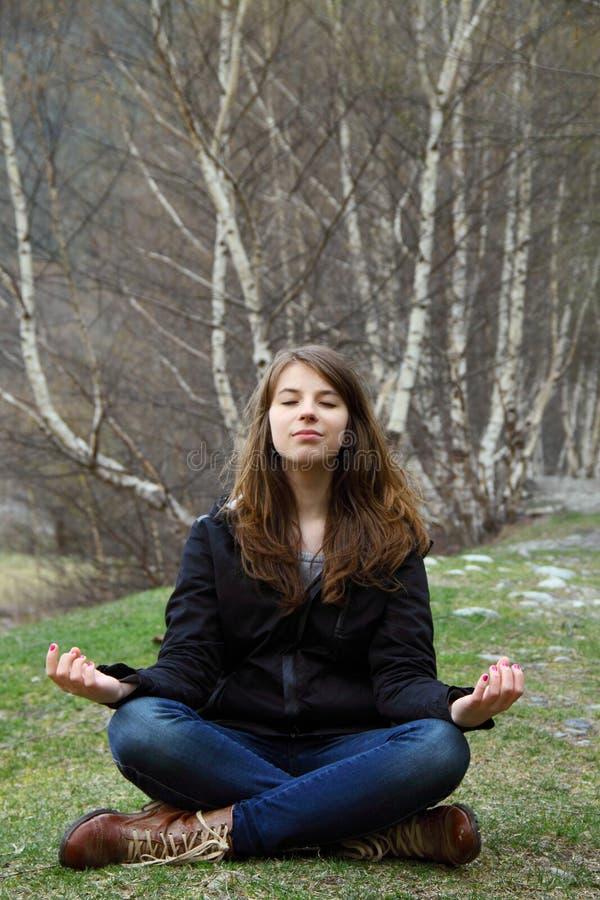 De jonge meisjeszitting op het gras en mediteert royalty-vrije stock afbeeldingen