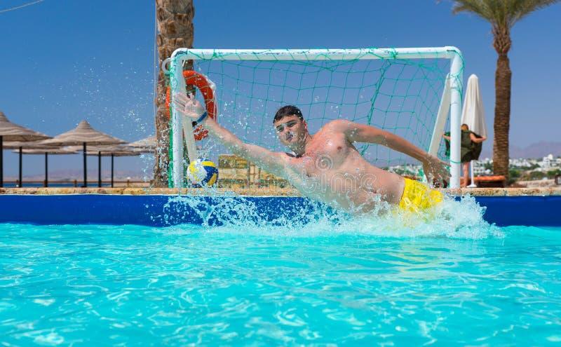 De jonge mens in actie slaat het doel in polo van het pool het speelwater over stock foto's