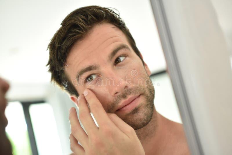 De jonge mens applyong roomt dagelijks af stock afbeelding
