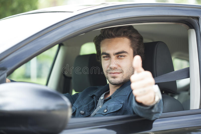 De jonge mens beduimelt omhoog gebaar in auto stock afbeeldingen
