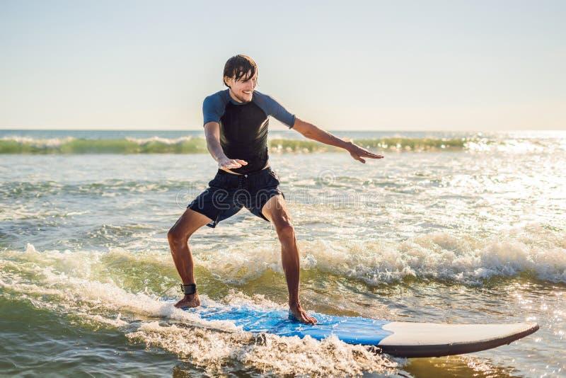 De jonge mens, beginnerssurfer leert om op een overzees schuim op B te surfen stock foto