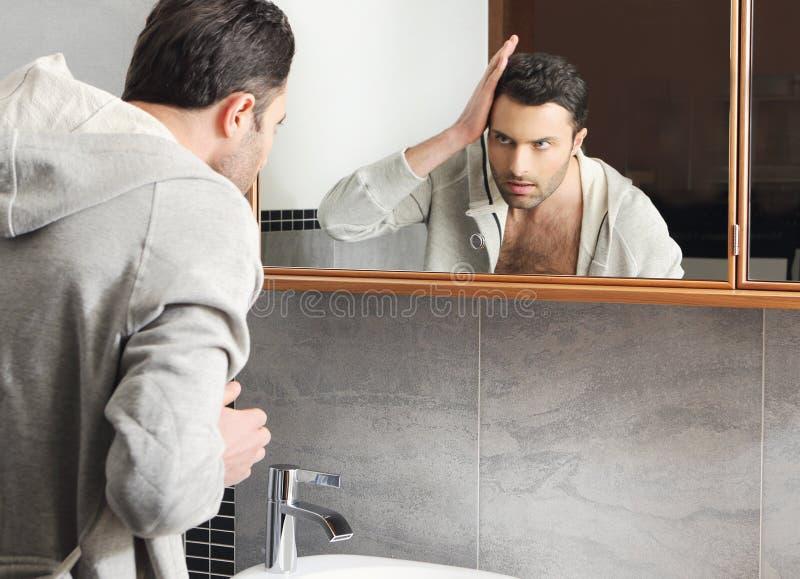 De mens bekijkt zich in de spiegel stock foto
