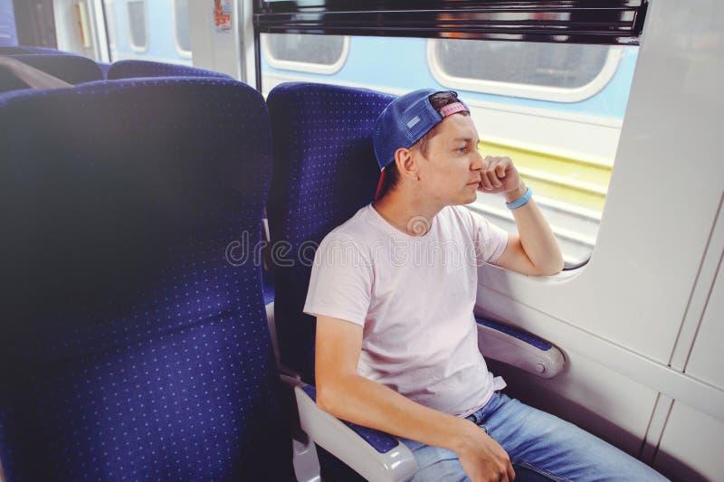 De jonge mens berijdt een trein, kijkt uit het venster, reis, comfortabele reisreis royalty-vrije stock fotografie