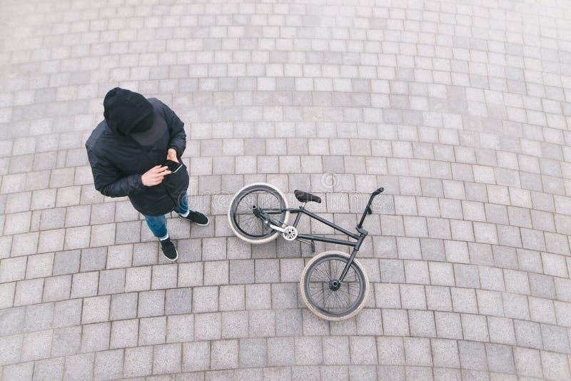 De jonge mens bevindt zich op de straat dichtbij een BMX-fiets en gebruikt een smartphone Rust na trucs op BMX Hoogste mening stock foto's