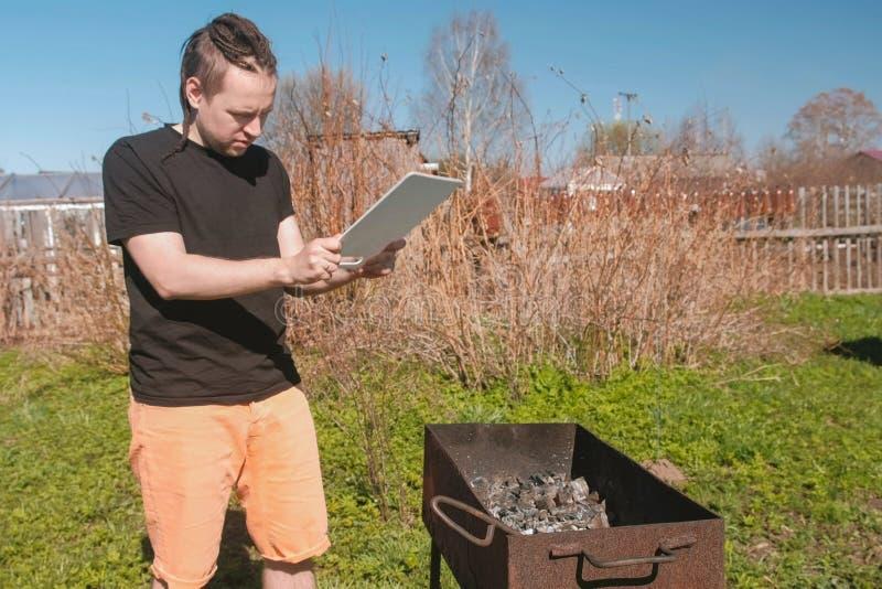 De jonge mens blaast de steenkolen in de grillkoperslager met op een scherpe Raad stock foto