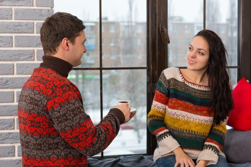 De jonge mens bracht koffie aan zijn vrouw terwijl zij zitting op venster stock afbeeldingen