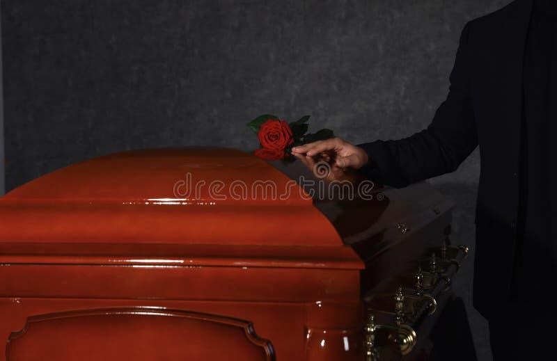 De jonge mens dichtbij kist met rood nam in rouwkamer toe royalty-vrije stock afbeeldingen