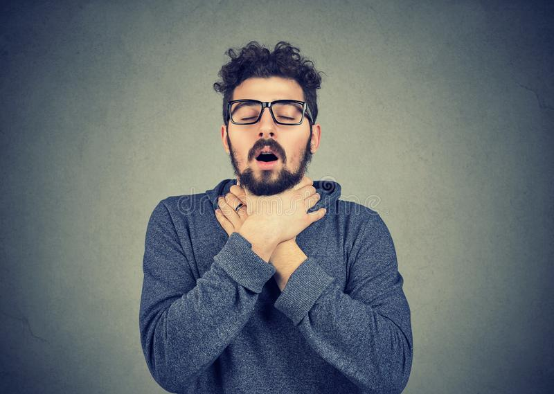 De jonge mens die astmaaanval hebben kan de adem van ` t stock fotografie