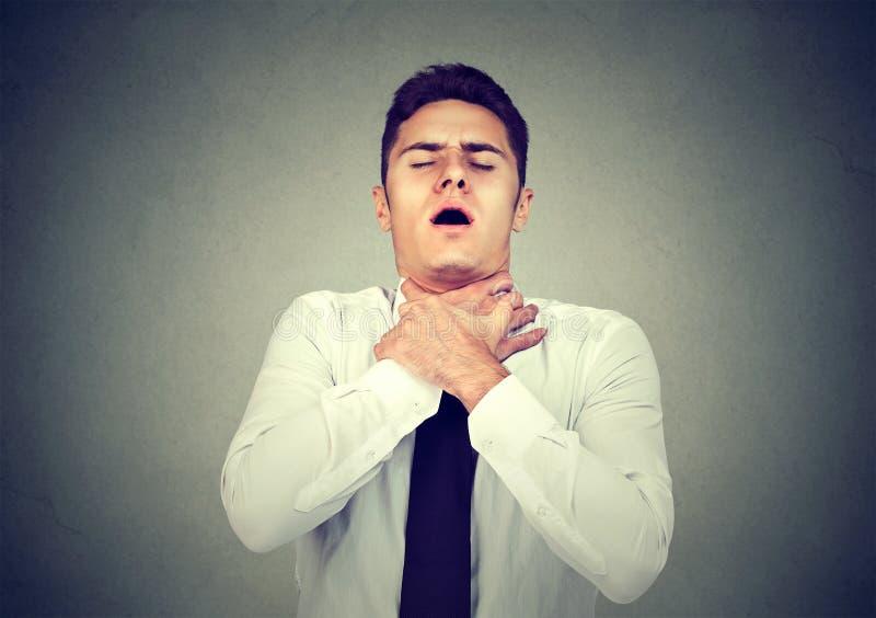 De jonge mens die astmaaanval hebben of kan de adem die van ` t aan ademhalingsproblemen lijden versperren royalty-vrije stock fotografie