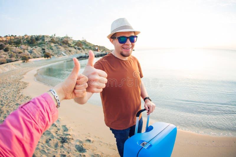 De jonge mens die bij de toevlucht aankomen en zich op het strand bevinden terwijl het tonen beduimelt omhoog stock foto's